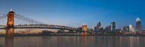 Photo of Cincinnati's skyline and the Roebling Suspension Bridge at dusk.