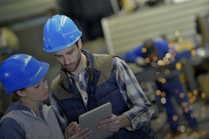 Man and woman wearing hard hats and looking at a tablet.