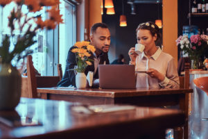 Photo of couple meeting over coffee and looking at a laptop computer.