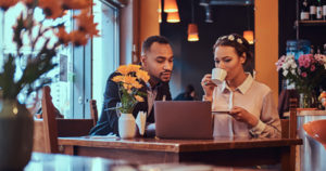 Photo of couple meeting over coffee and looking at a computer.