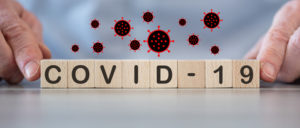 "Photo of ""COVID-19"" spelled in scrabble tiles with illustrated viruses floating above"
