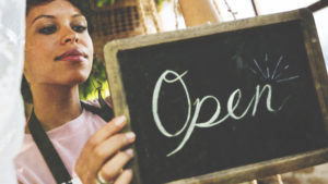 "Woman of color putting a chalkboard sign reading ""open"" in a window."