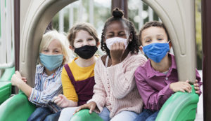 A multi-ethnic group of four children, 5 to 7 years old, playing together on a playground during school recess. They are sitting side by side on two slides, looking at the camera. They are all wearing masks, back to school during the COVID-19 pandemic. .